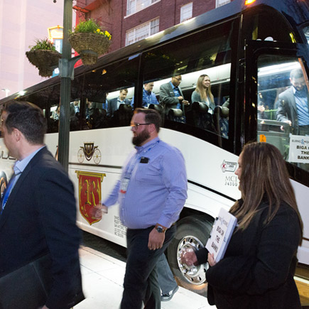 A group of event attendees exiting a parked coach bus