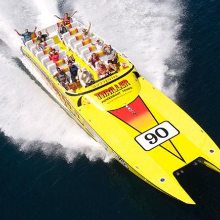 Group of people holding up their hands on a yellow speedboat during a powerboat tour on the ocean
