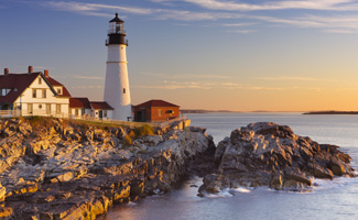 A lighthouse in the Northeast USA sitting on the edge of a peninsula surrounded by water at sunrise